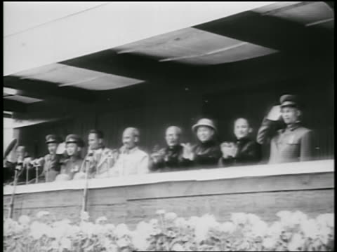 B/W 1950s Ho Chi Minh surrounded by others standing on balcony / North Vietnam / newsreel