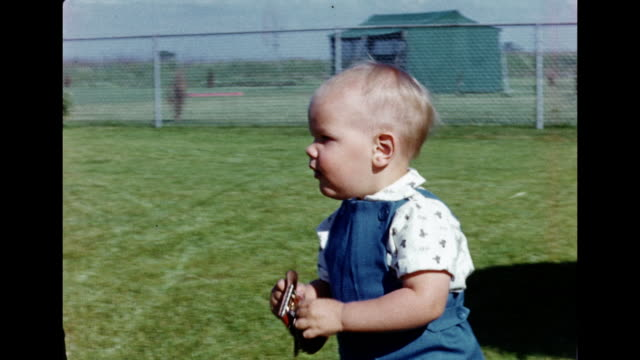 1950s HOME MOVIE Baby boy walking around front yard then looks at camera