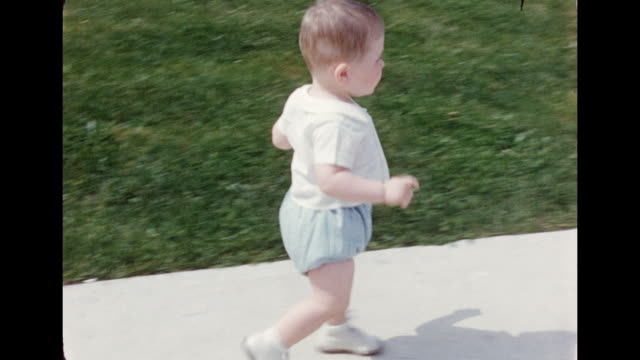 1950s home movie baby boy walking around on driveway - middle class stock videos and b-roll footage