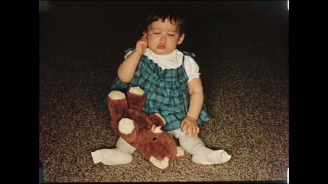 1950s home movie baby girl sitting on a carpeted living room floor with her teddy bear - teddy bear stock videos & royalty-free footage