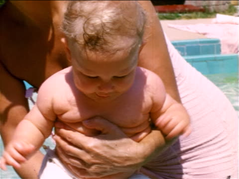 1950s home movie close up mother standing in swimming pool holding baby - ワンピース型の水着点の映像素材/bロール