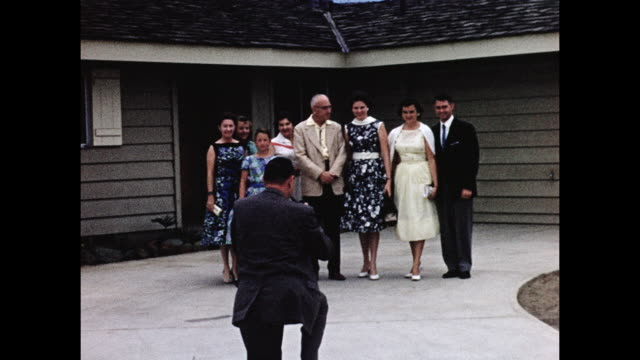 vidéos et rushes de 1950s home movie - family poses for picture in front of their home - prendre une photo