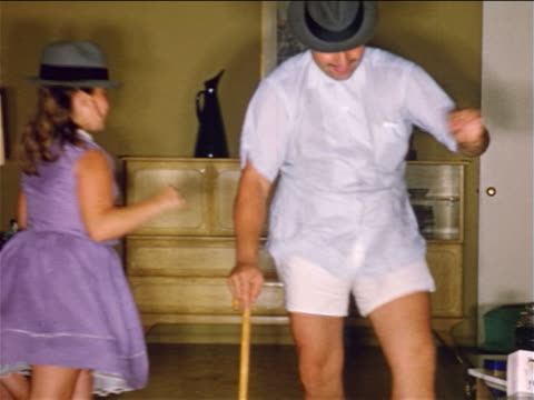 vidéos et rushes de 1950s home movie father + daughter with hats + mustaches dancing + acting silly - deux parents