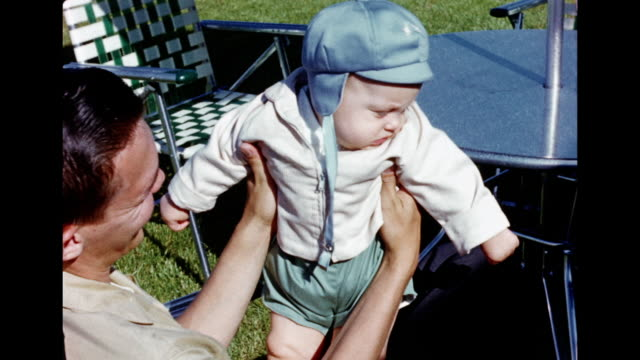 1950s HOME MOVIE Father holding up baby boy