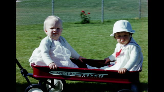 1950s HOME MOVIE Father pulling red radio flyer wagon with crying babies