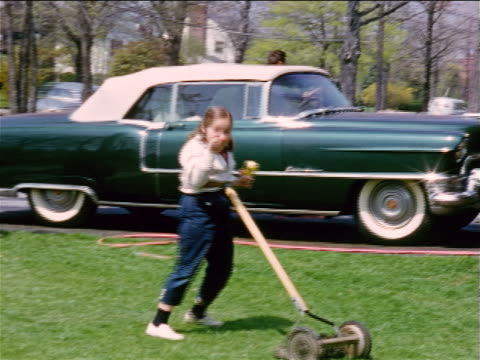 1950s home movie pan girl mowing yard with push lawnmower waving to camera / green car in background - gardening stock videos & royalty-free footage