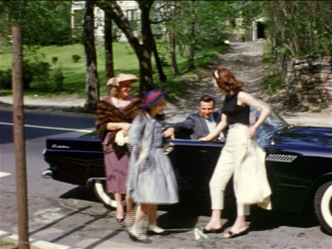 1950s home movie girl + woman in dresses + hats posing with woman by black 1958 t-bird convertible - thunderbirds stock videos and b-roll footage