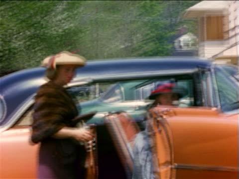 vídeos de stock e filmes b-roll de 1950s home movie girl + woman wearing dresses + hats climbing into pink cadillac + waving to camera - cadillac