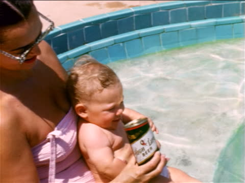 1950s HOME MOVIE mother + baby sitting in swimming pool / baby sipping from beer can