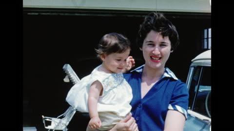 vidéos et rushes de 1950s home movie mother carrying her baby - stéréotype de la classe moyenne