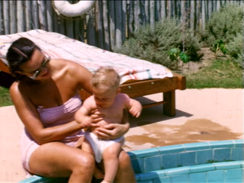 1950s home movie mother in bathing suit sitting at swimming pool edge dipping baby into water - ワンピース型の水着点の映像素材/bロール