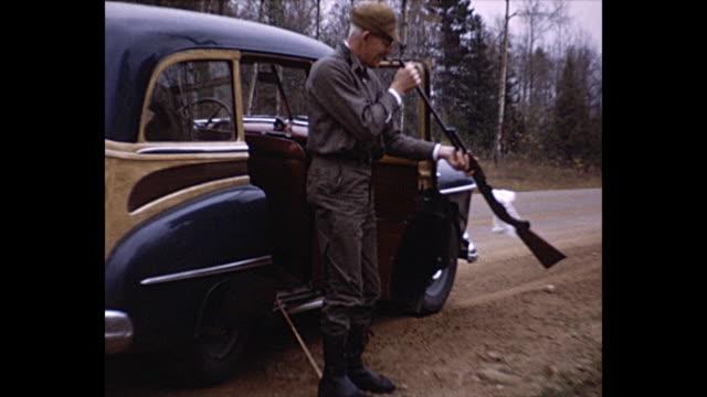 1950s Home Movie  - Various shots of men firing rifles, men looking down a rifle barrel