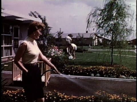 1950s WS homeowner watering plants / Levittown, Pennsylvania, United States