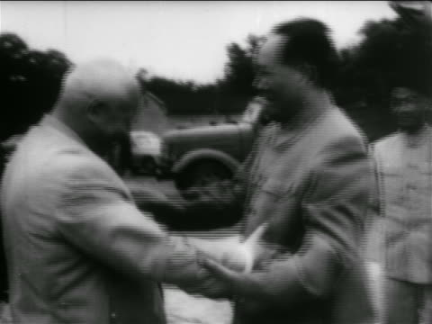 B/W 1950s Khrushchev Chairman Moa hugging shaking hands outdoors / newsreel