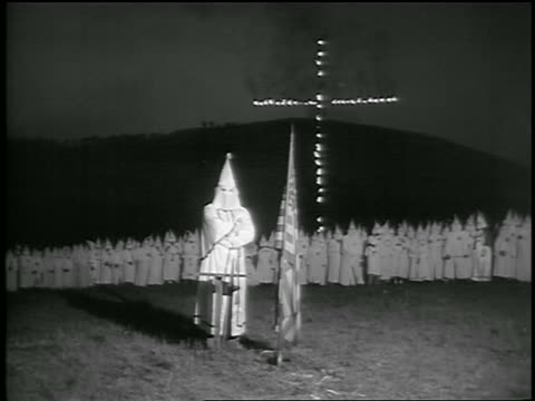 vídeos de stock, filmes e b-roll de b/w 1950s ku klux klan member stands by us flag / crowd of kkk members burning cross in background / ga - ku klux klan