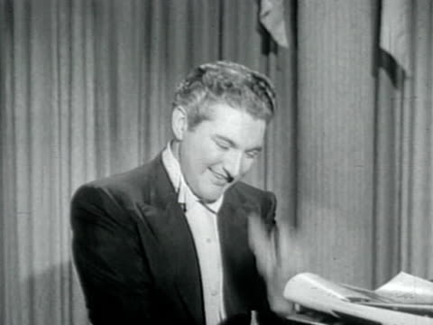 1950s MS Liberace playing piano and talking to camera
