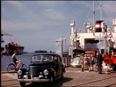 1950s line of cars driving off ferryboat / people standing near ramp / denmark - ferry stock videos & royalty-free footage