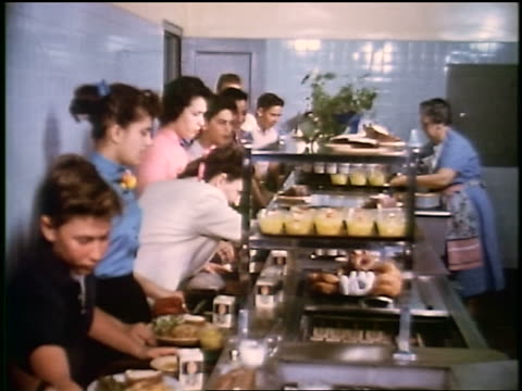 1950s line of children/teens getting food in school cafeteria / tilt down to boy's hand paying + tray