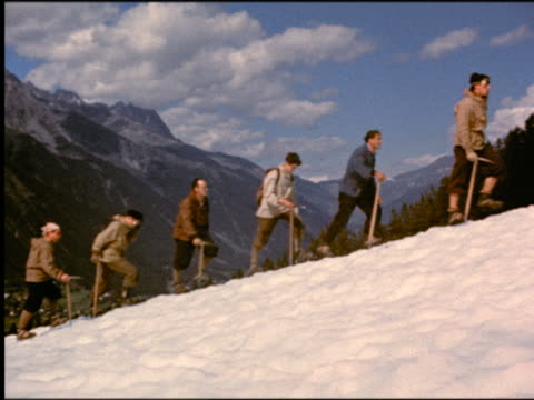 stockvideo's en b-roll-footage met 1950s line of men carrying pick-axes walking up snowy slope of mountain / (mont blanc?) / italian alps / italy - 1955