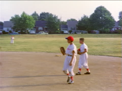 vidéos et rushes de 1950s pan little league baseball players in uniforms taking positions + practicing catching - casquette de baseball