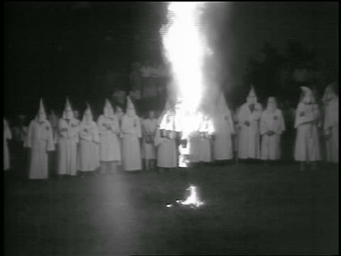 vídeos de stock, filmes e b-roll de b/w 1950s long shot burning cross with crowd of ku klux klan members standing in background at night / georgia - ku klux klan