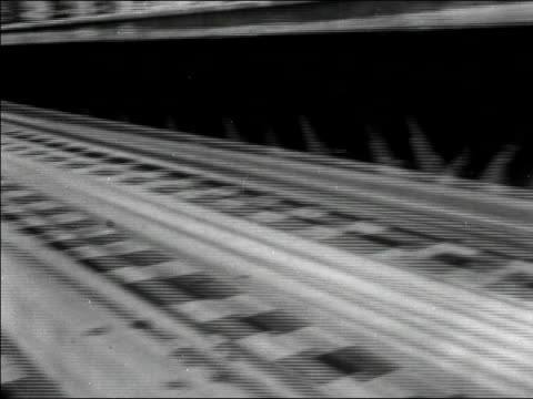 1950s low angle close up elevated train wheels rolling on track/ pan to wide shot train rolling away from camera/ new york city/ audio - hochbahn passagierzug stock-videos und b-roll-filmmaterial