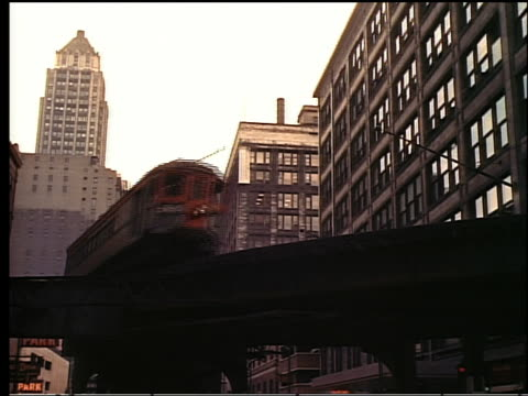 1950s low angle elevated train turning corner on tracks with buildings in background / Chicago
