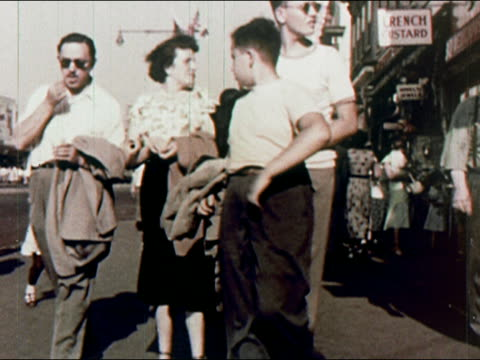 1950s low angle medium shot family walking along crowded coney island / brooklyn, new york / audio - coney island stock-videos und b-roll-filmmaterial