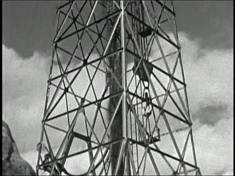 stockvideo's en b-roll-footage met 1950s low angle medium shot tilt up derrick gushing oil - bouwapparatuur
