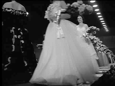 vídeos de stock, filmes e b-roll de b/w 1950s low angle miss america beauty contestants walking on stage carrying bouquets - rainha de beleza
