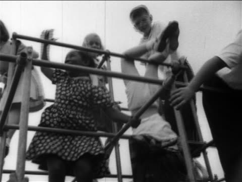 vídeos de stock, filmes e b-roll de b/w 1950s low angle pan schoolchildren, black + caucasian, playing together on jungle gym / newsreel - jungle gym