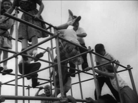 vídeos de stock, filmes e b-roll de b/w 1950s low angle schoolchildren, black + caucasian, playing together on jungle gym / newsreel - jungle gym