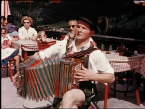 1950s man in traditional austrian costume playing accordion on restaurant patio - hängslen bildbanksvideor och videomaterial från bakom kulisserna