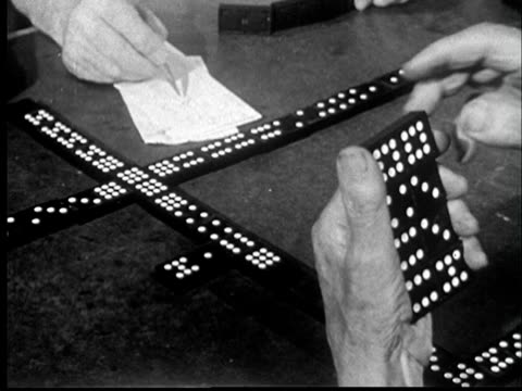 """""""1950s cu pov man's hand holding dominoes as he figures out next move and man across table writes down game score/ st. louis, missouri"""" - unknown gender stock videos & royalty-free footage"""