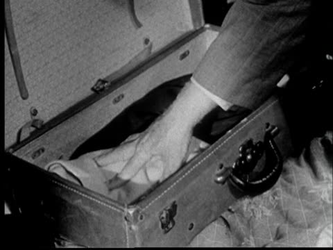'1950s CU Man's hands packing suitcase/ St. Louis, Missouri'