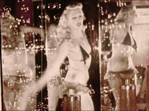 1950s medium shot burlesque dancer wearing bra and panties dancing surrounded by bubbles and mirrors / coney island / brooklyn, new york / audio - sinnlichkeit stock-videos und b-roll-filmmaterial