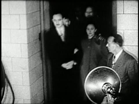 vídeos de stock, filmes e b-roll de 1950s medium shot ethel julius rosenberg leaving court together arminarm amid flashing bulbs - de braços dados
