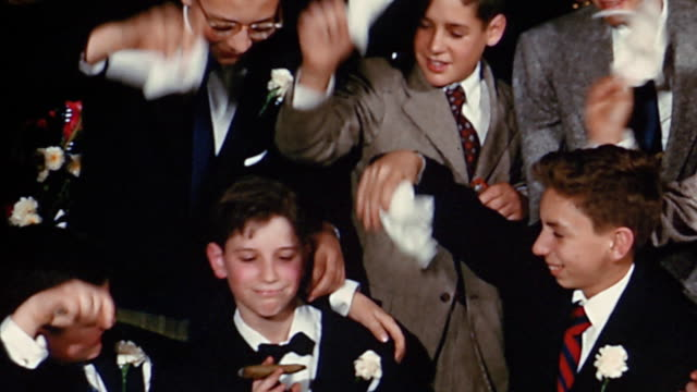 vidéos et rushes de 1950s medium shot group of boys using handkerchiefs to fan boy smoking cigar - grimace de pitre