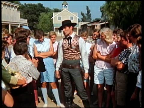 1950s medium shot hugh o'brian talking to tour group on set of tv series 'wyatt earp' / drawing pistol at cam - fame stock videos & royalty-free footage