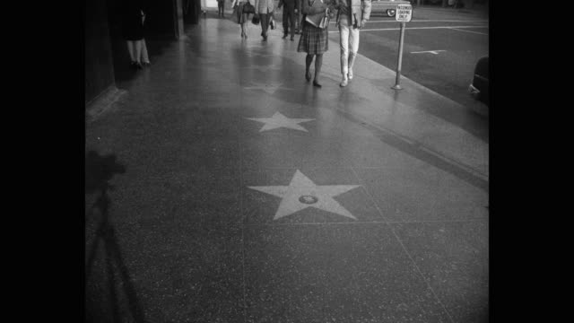1950s - medium shot of pedestrians walking on walk of fame on hollywood boulevard, hollywood, los angeles, california, usa - star shape stock videos & royalty-free footage