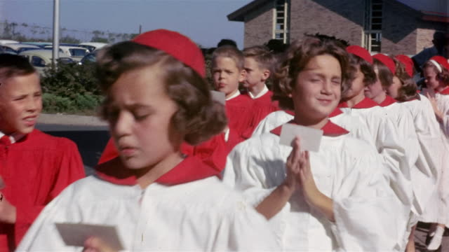 1950s medium shot procession of young girls and boys in confirmation robes putting palms together in prayer - catholicism stock videos and b-roll footage