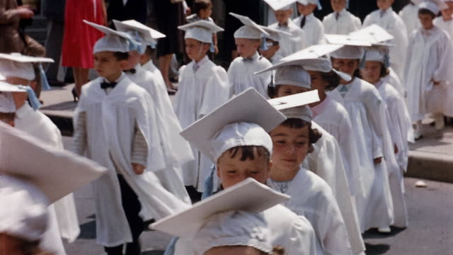 1950s medium shot procession of young girls and boys in white caps and gowns at commencement - katholizismus stock-videos und b-roll-filmmaterial