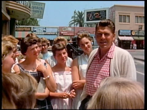 1950s medium shot Ronald Reagan talking to teenage girls / Los Angeles CA