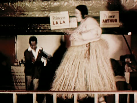 "1950s medium shot small man (prince arthur) wearing suit and large woman (princess la la) wearing hula skirt and bra dancing together on stage / ""not all the pretty girls are single"" / coney island, brooklyn, new york / audio - coney island stock-videos und b-roll-filmmaterial"
