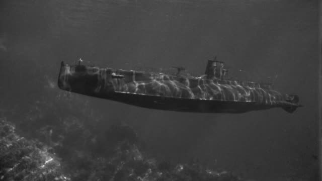 1950s medium shot submarine moving underwater / staged - sottomarino subacqueo video stock e b–roll