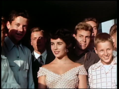 vídeos de stock e filmes b-roll de 1950s medium shot teenage elizabeth taylor surrounded by young men - 16 17 anos