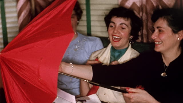 1950s medium shot woman sitting next to two women on couch opening red umbrella and holding over heads
