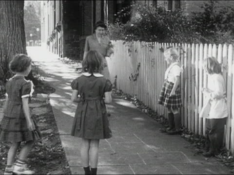 1950s medium shot woman walking on sidewalk / playing hopscotch / young girls jumping with her / AUDIO