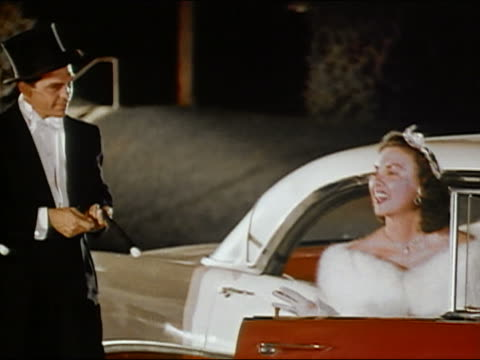 1950s medium shot woman wearing white fur and tiara exiting red car / man in tuxedo admiring her / AUDIO
