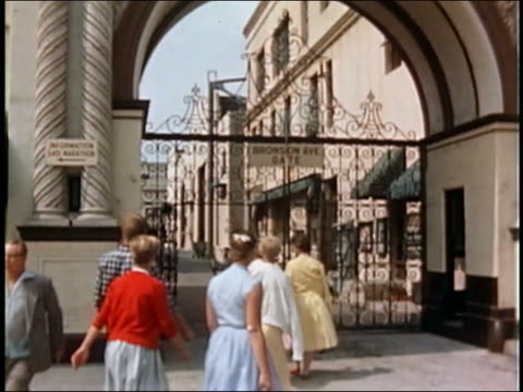 1950s medium shot Women entering Paramount gate / tilt up Paramount Pictures sign on top of gate / Hollywood, CA
